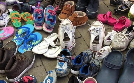 Philadelphia immigration protesters line up empty children's shoes near Mike Pence's hotel